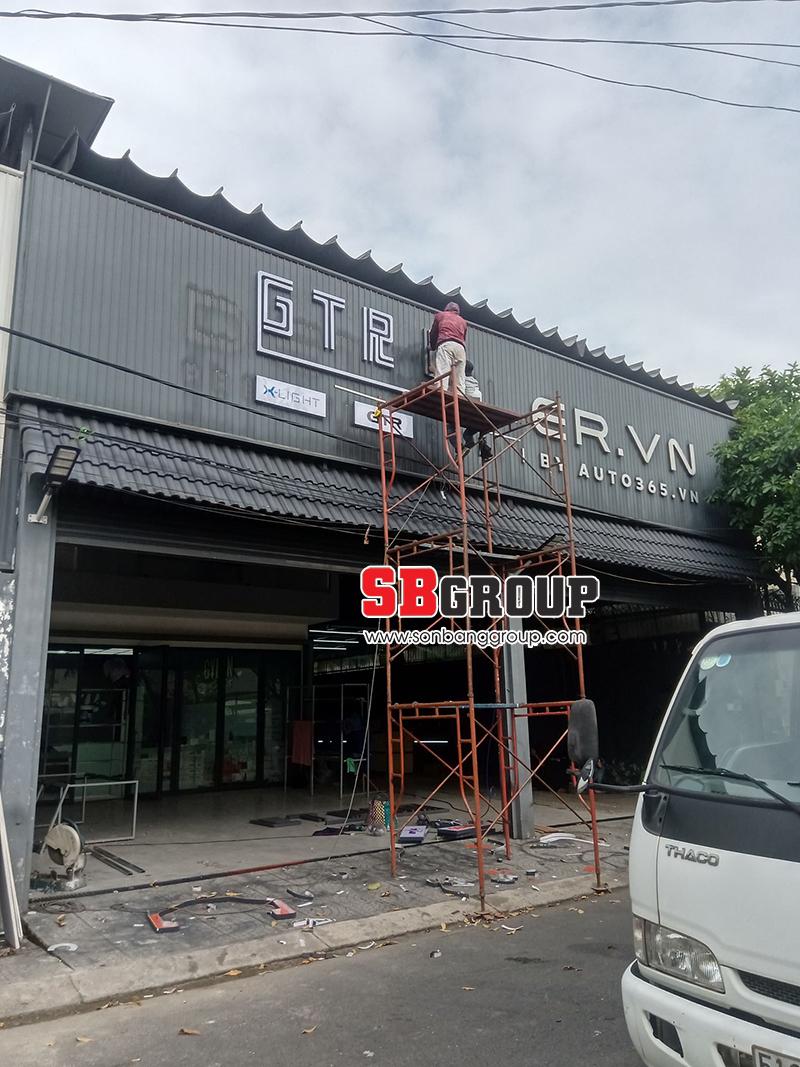 SBGROUP đang thi công dán chữ mica trên mặt bảng hiệu tôn sơn đen tĩnh điện